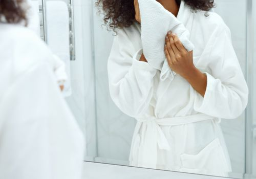 Woman washing her face in mirror