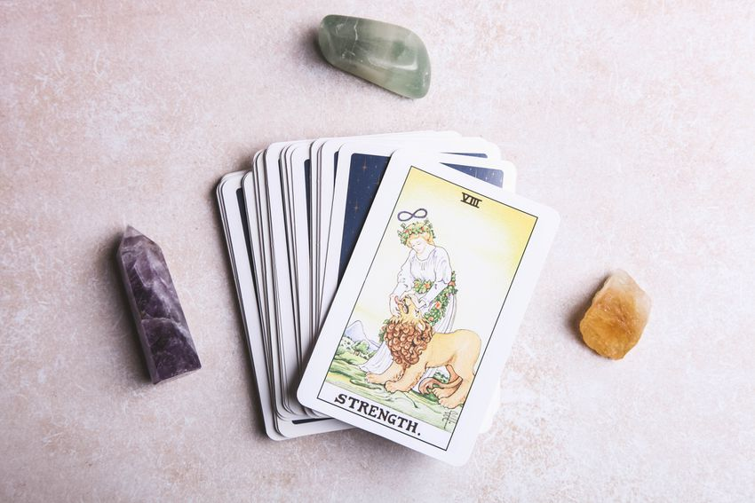 Tarot deck with the strength card face up on top surrounded by crystals
