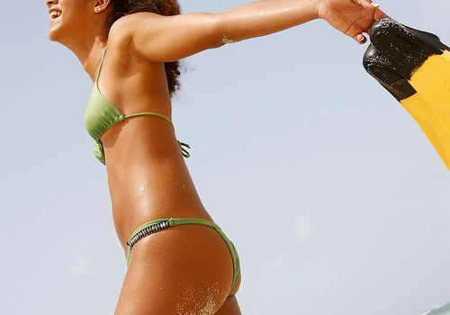 young mixed woman in bikini at the beach