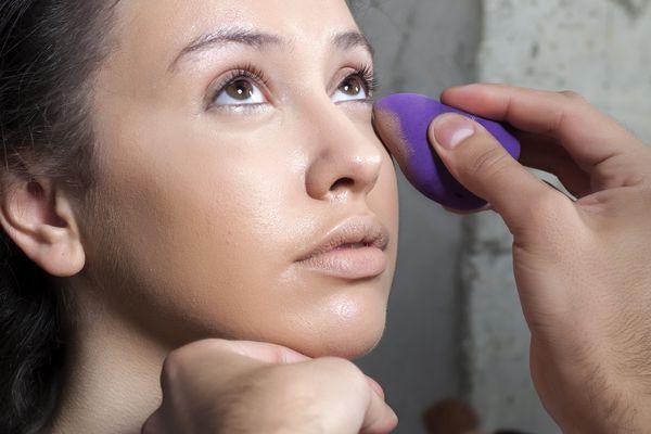 woman applying makeup with sponge