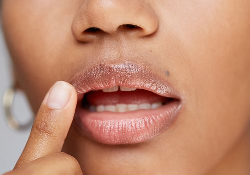 woman touches her glossy lips
