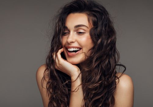 Woman with semi-wet curly hair smiling