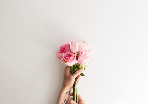 Roses in the hands of someone with tattoos on their wrists