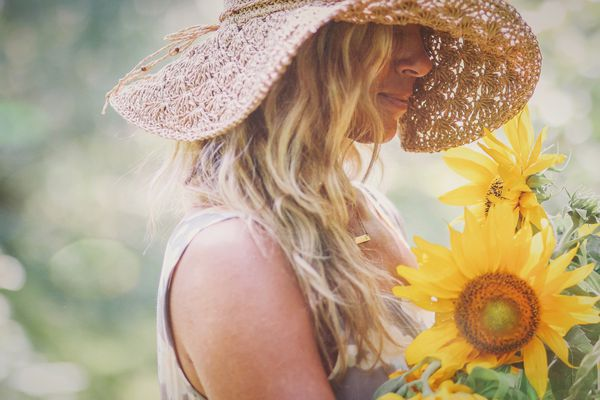 Blonde woman with a sun hat and sunflowers
