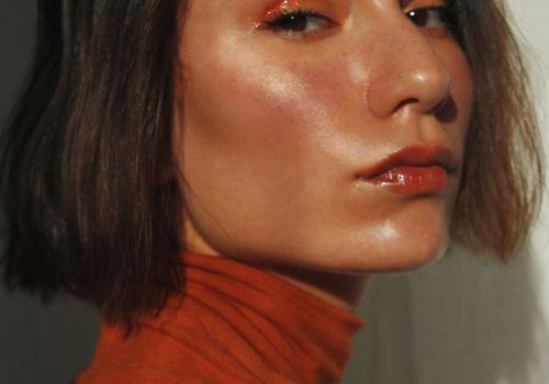 closeup of brunette woman in orange turtleneck sweater