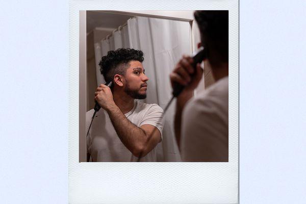 man trimming hair at home