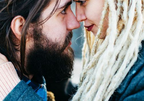 woman with bleached dreadlocks and man with beard nuzzling each other