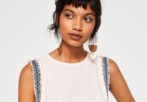 Woman with gold earrings and vest top