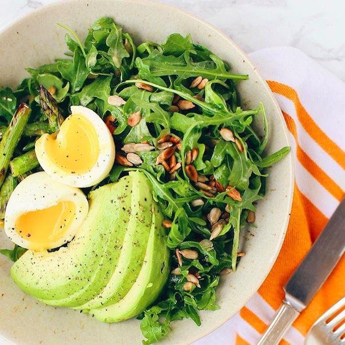 Arugula salad topped with boiled egg, avocado, and asparagus