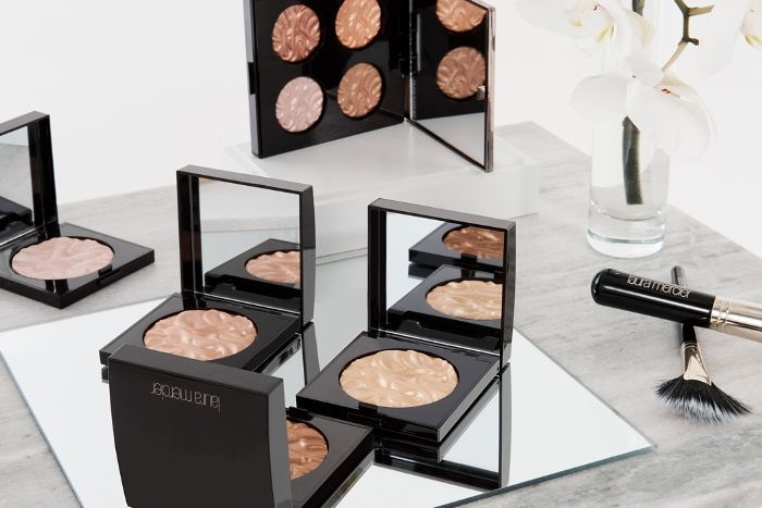 Laura Mercier pallates and highlighters spread out on a table