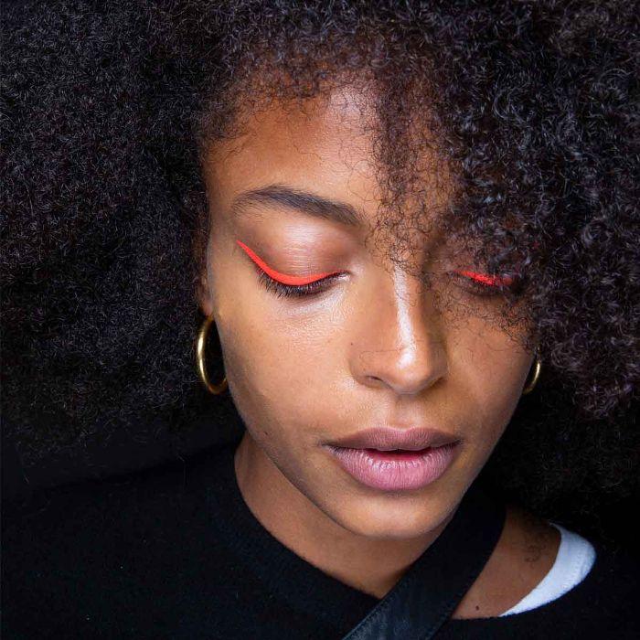 Model wearing orange neon eyeliner
