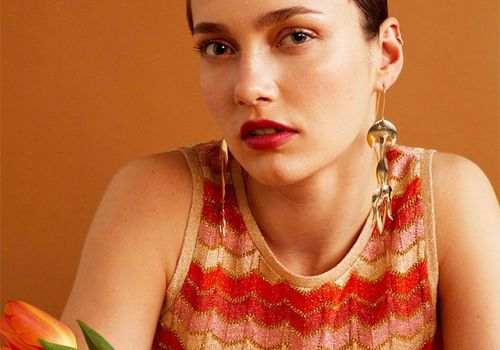 woman with slicked down brown hair in a red pink and gold chevron shirt wearing gold earrings over a burnt orange background with a tulip in front of her