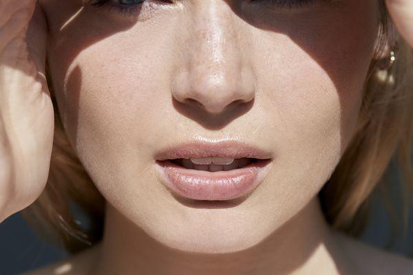 Woman shielding face from hot summer sun