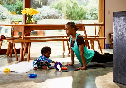 person exercising with infant beside