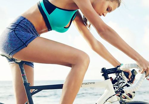 woman on bicycle in workout clothes