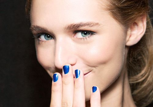 woman smiling with blue nail polish