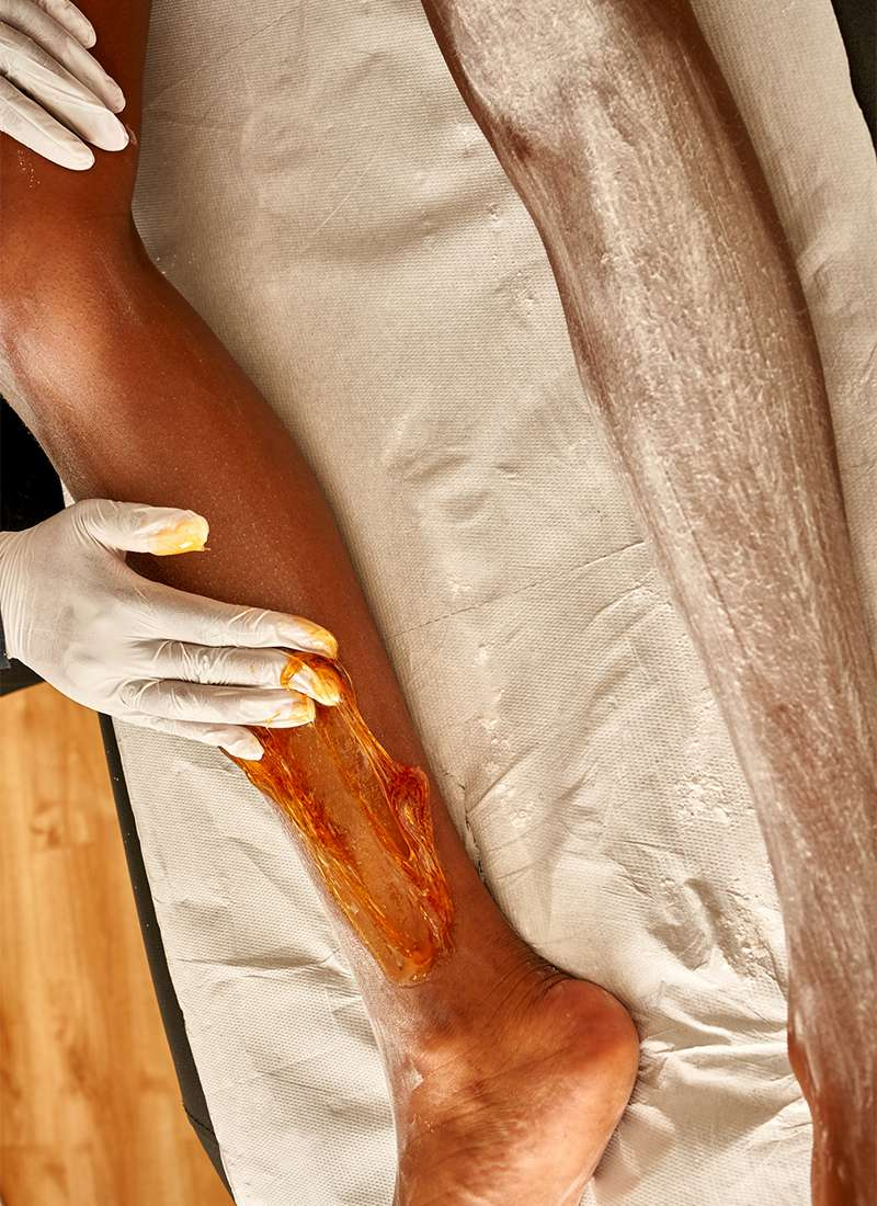 beautician applying sugaring wax to leg of client