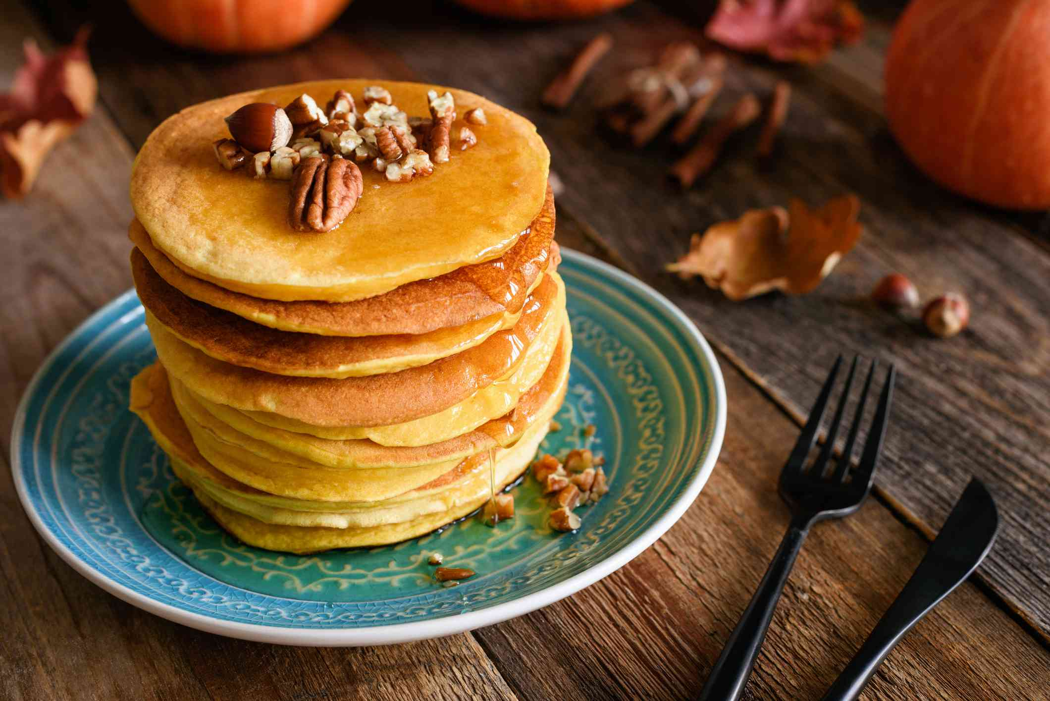Stack of homemade pumpkin pancakes with pecan nuts on top. Wooden table background, black stylish cutlery.