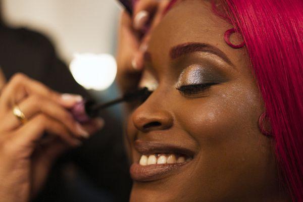Woman putting mascara on woman