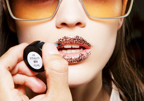 woman getting glitter lipstick applied to lips