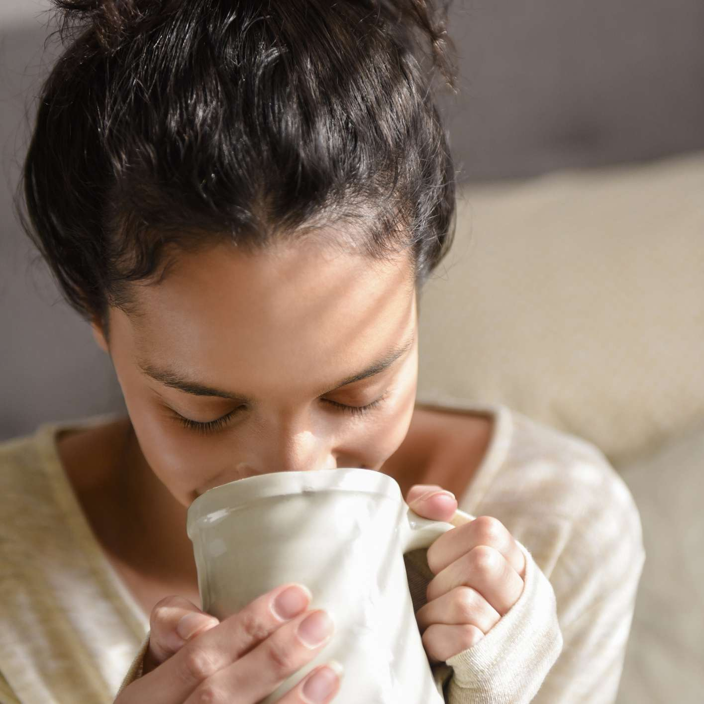 woman sipping coffee from a mug