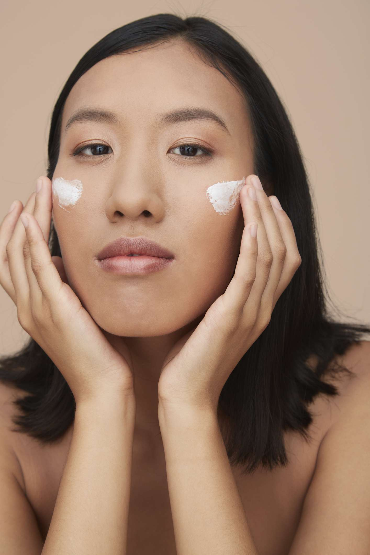 woman applying creme to face