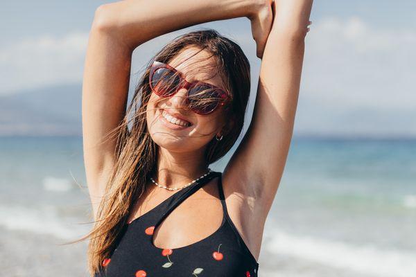 woman with her arm raised in a bikini