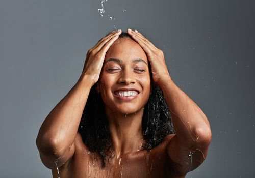 woman with water falling on her head as she touches her scalp