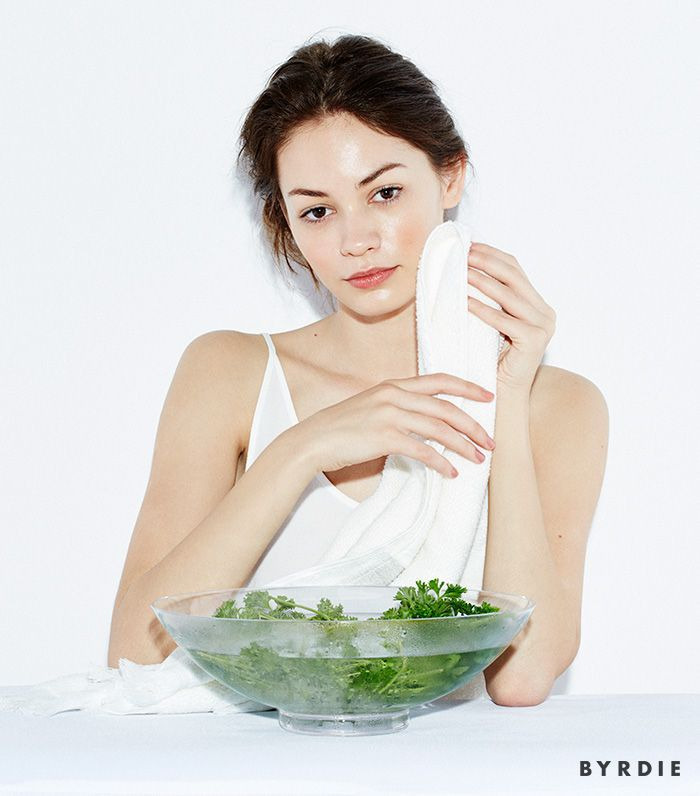 model with bowl of herbs in water and towel on cheek