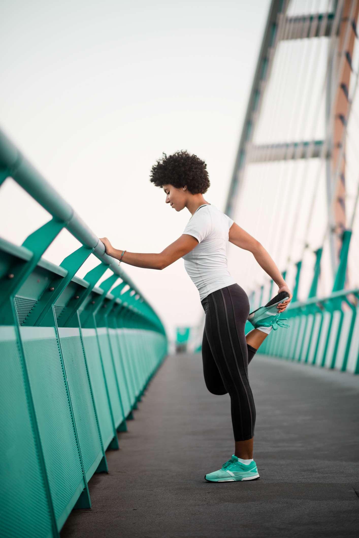 woman on bridge stretching