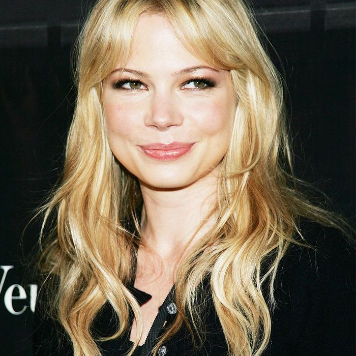 Michelle Williams with long, wavy hair and bangs on a red carpet