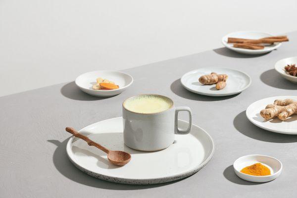 Milk, turmeric, ginger, and cinnamon on a gray table.