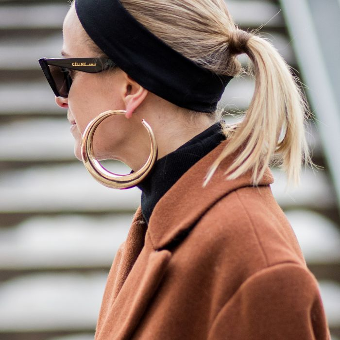 how to wear a headband: Woman wearing black headband with ponytail