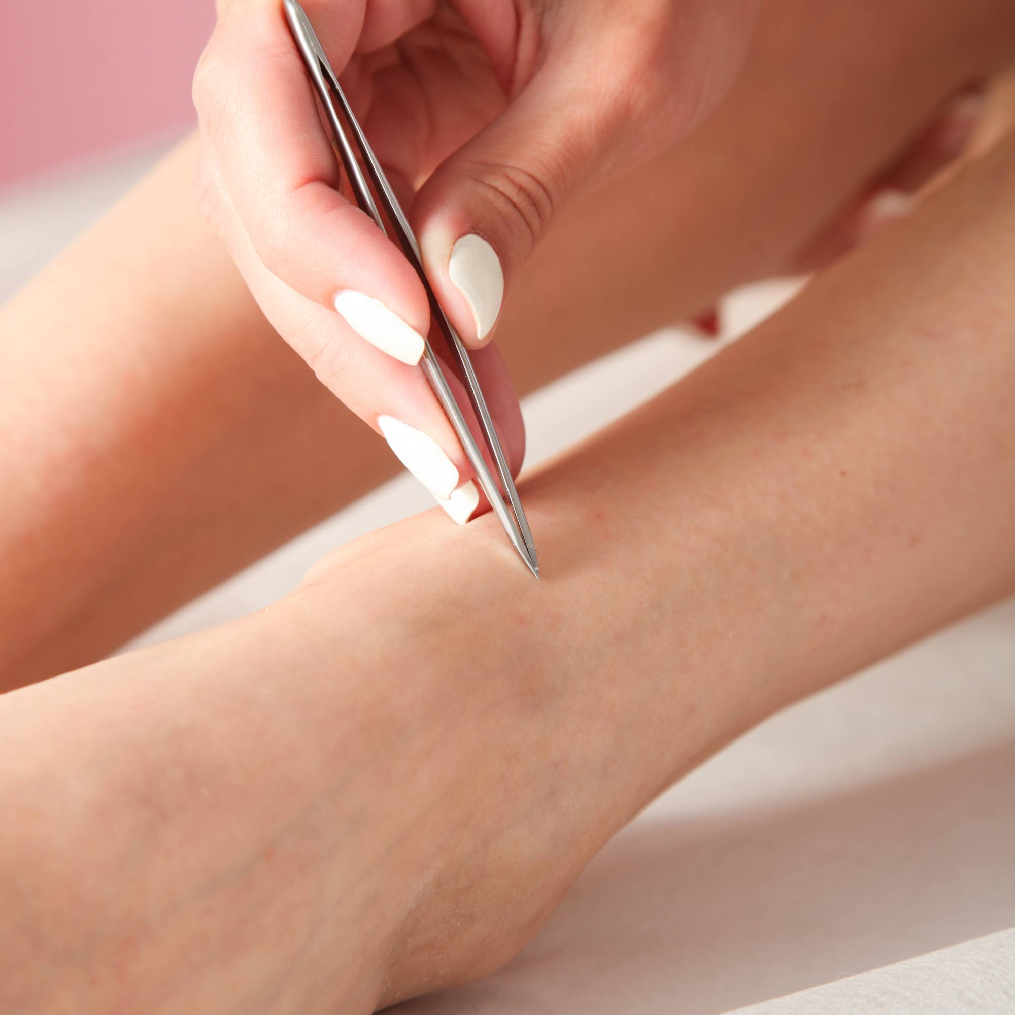 person tweezing leg hair