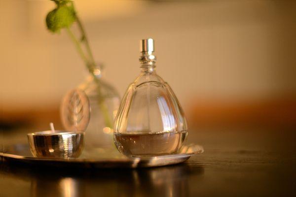 Perfume bottle next to tealight on table