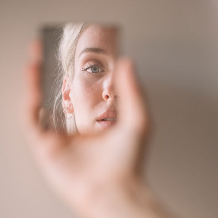 Woman looking in a hand mirror