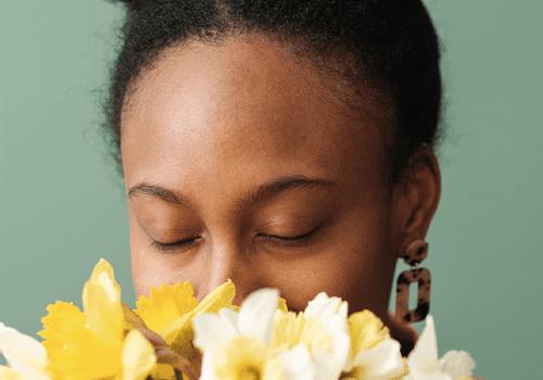 woman melling flowers