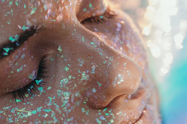 woman with glitter on face and eyes closed