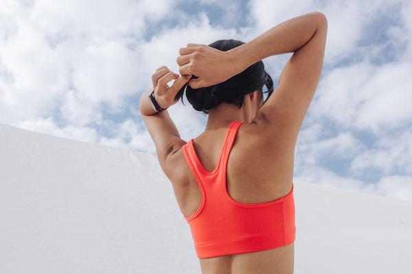 woman putting hair up in orange sports bra