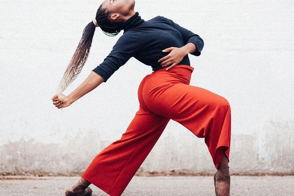 Dejah Poole wearing red wide-leg pants and striking a pose
