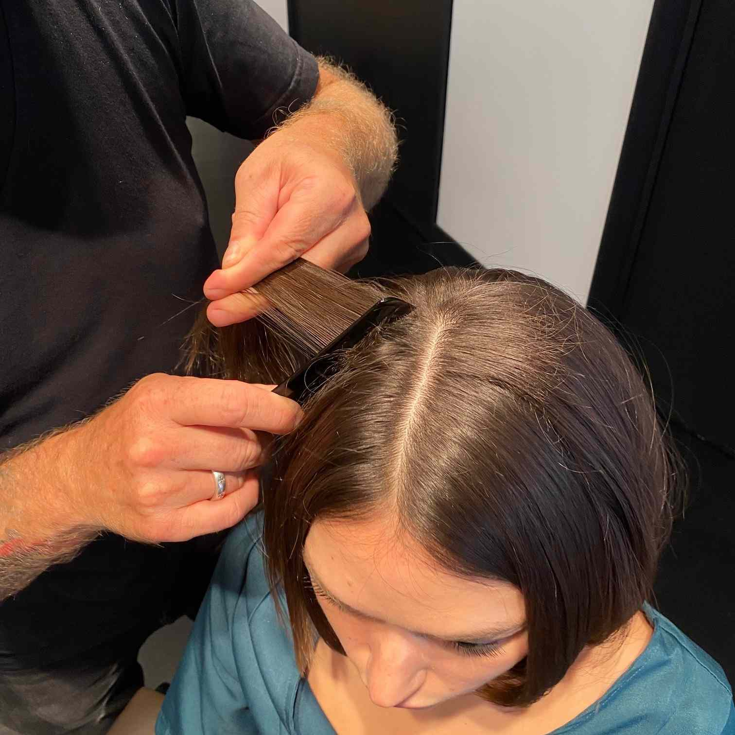 Hairstylist teasing client's hair with a comb