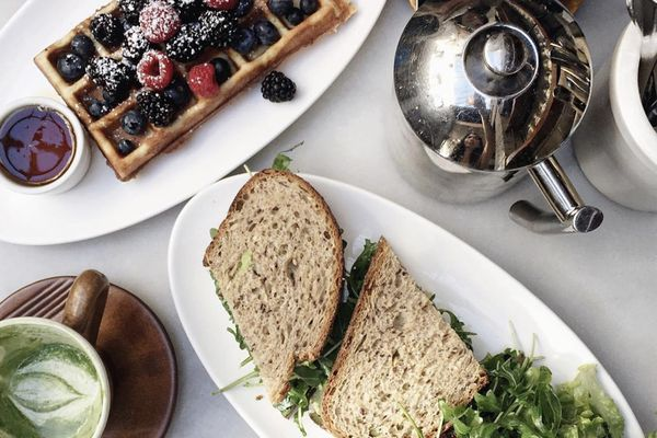 Table top with waffles and berries; sandwich halves with salad; matcha cup; tea cup; and tea kettle