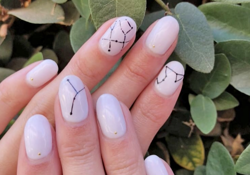 olive and june zodiac manicure against tree