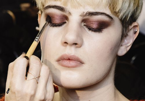 Makeup artist applying red eye shadow to model