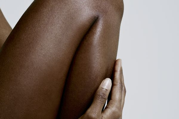 woman holding leg against gray background