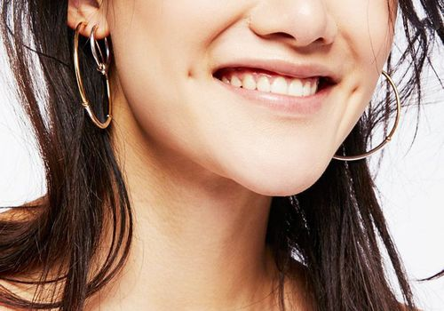 smiling young asian woman with hoop earrings and dimples