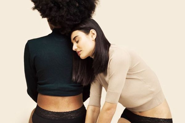 Two women knealing wearing Thinx underwear, one leaning on the other