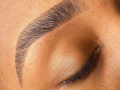 Close-up of woman's tinted eyebrow with eyes closed