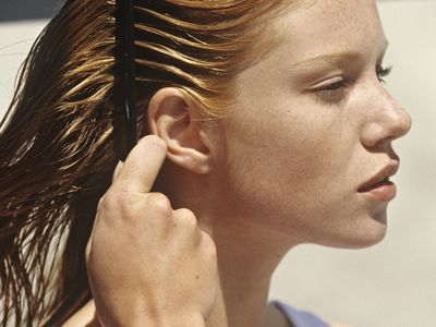 Red haired woman combing her hair in the sunlight.