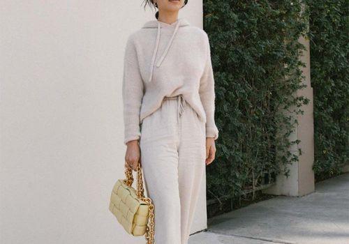 Woman in beige loungewear with a yellow handbag